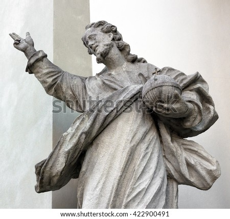 Statue of God; in his hand he holds the planet Earth. - stock photo