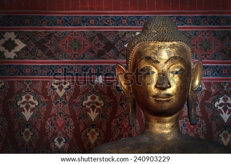 Statue of golden Buddha over mural painting in the temple of Buddhist in Thailand. - stock photo