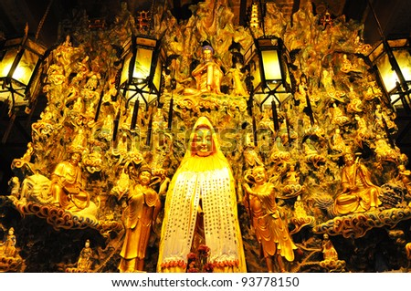 Statue of Guan yin with hundred god in background - stock photo