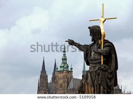 statue of Jesus carrying a golden cross touching the tip of the roof of Prague Castle - stock photo