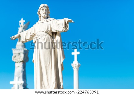 Statue of Jesus Christ with his arms extended and christian crosses on the background - stock photo
