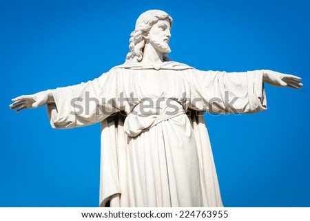 Statue of Jesus Christ with his arms extended on a clear blue sky background - stock photo
