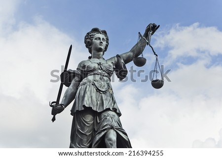 Statue of Justice with sword and scales in front of a blue cloudy sky - stock photo