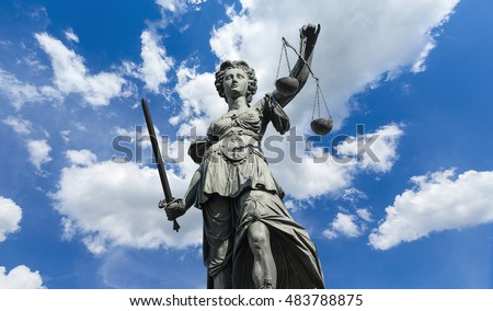 Statue of Justitia (justice goddess) on cloudy blue sky