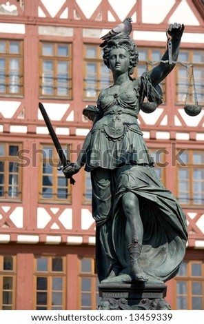 Statue of Lady Justice with a sleeping pigeon - stock photo