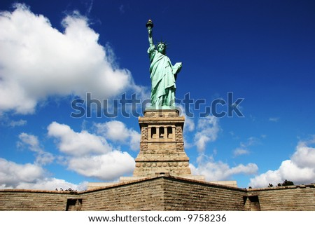 Statue Of Liberty against deep blue sky and clouds - stock photo