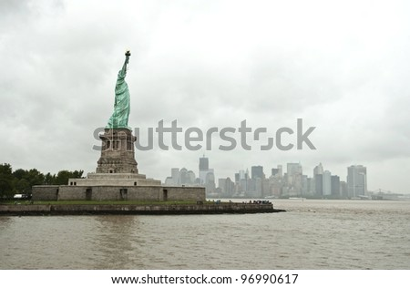 Statue of Liberty and New York City Skyline in background on a rainy day,  Freiheitsstatue und New York City Skyline im Hintergrund an einem regnerischem Tag, Manhattan, USA - stock photo