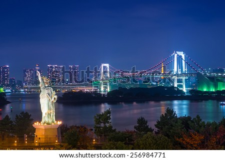 Statue of Liberty and Rainbow bridge at Odaiba Tokyo in twilight - stock photo