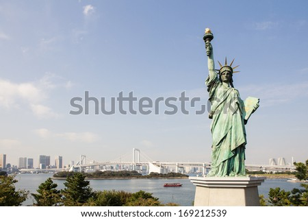 Statue of liberty at Odaiba, Tokyo, Japan with background of rainbow bridge across Tokyo bay. Blue sky and little cloud. - stock photo
