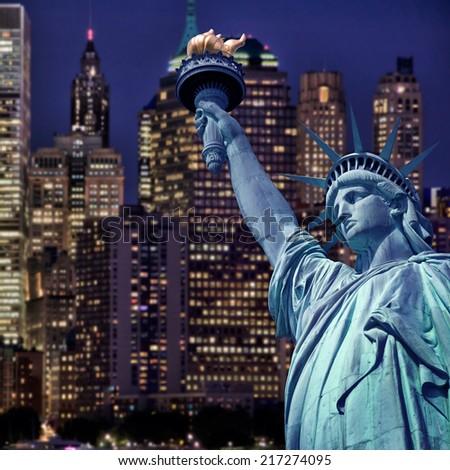 Statue of liberty by night, New York skyline background - stock photo