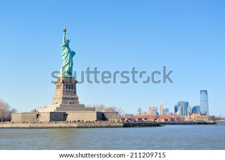 Statue of Liberty faces New York City Manhattan downtown skyline with skyscrapers over Hudson River with clear blue sky. - stock photo