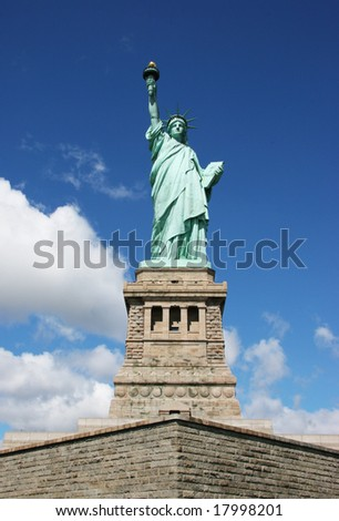 Statue of liberty front view with blue sky and clouds