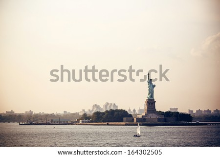 Statue of Liberty in New York at sunset - stock photo