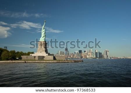 Statue of Liberty on Liberty Island in front of the Manhattan Skyline on a summer day with blue sky, New York City, USA, Freiheitsstatue vor der Skyline von Manhattan an einem sonnigen Sommertag - stock photo