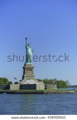 Statue of Liberty on Liberty island seen from Atlantic Ocean waters - stock photo