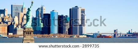 Statue of Liberty overlooking lower manhattan, the Brooklyn Bridge and New York Harbor. - stock photo