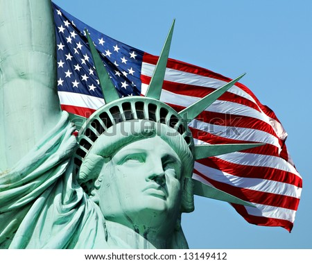 Statue of Liberty with a large american flag in the background. - stock photo