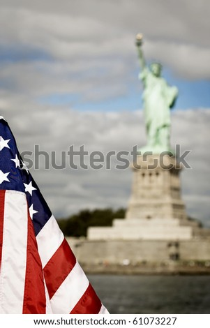Statue of Liberty with American flag in the foreground - stock photo