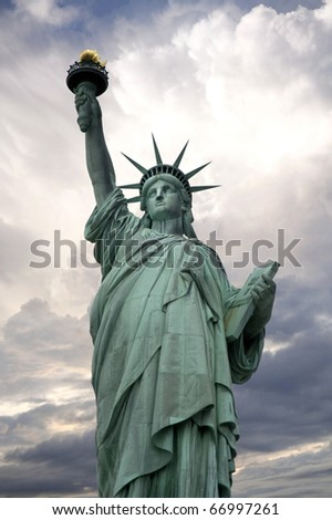 statue of liberty with dramatic clouds in the background - stock photo