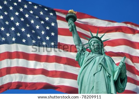 Statue of Liberty with the U.S. flag in the background. - stock photo