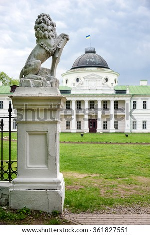Statue of lion holding a shield in its paws. Regal lion leaning on empty heraldic shield near the castle entrance. The palace and park complex Manor Tarnowski, s.Kachanovka, Ukraine - stock photo