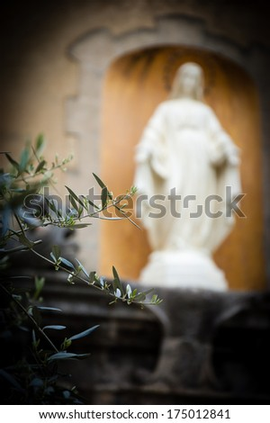 Statue of Madonna with stars nimbus on the front of Cathedral of Notre Dame of Assumption in Entraveaux (Alpes de Haute Provence, France) and olive tree at foreground. Selective focus on the tree.  - stock photo