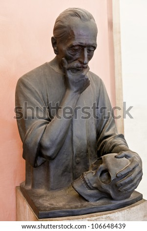 Statue of man holding skull - stock photo