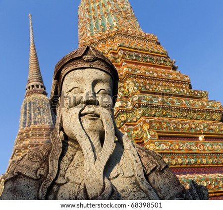 Statue of Man in Front of Colorful Stupas at Wat Pho in Bangkok, Thailand, Southeast Asia - stock photo