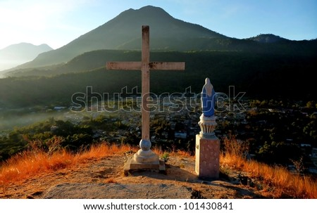 Statue of Mary next to the cross above San Pedro village at the lake Atitlan in Guatemala - stock photo
