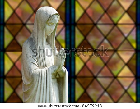 Statue of Mary praying in profile with isolation path and out of focus window as background - stock photo