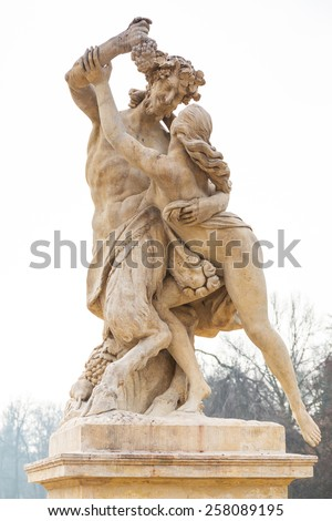 Statue of nymph catching grapes from satyr's hand in Lazienki park (Royal Baths park), Warsaw, Poland - stock photo