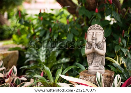 Statue of prayer in tropical garden. Calm colorful asia image