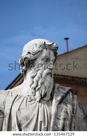 Statue of Saint Paul the Apostle with the chimney of Sistina Chapel on the background. Vatican City State - stock photo