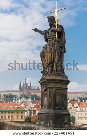 Statue of St. John the Baptist, the sculpture of Charles Bridge in Prague (Czech Republic) at cloudy morning. - stock photo