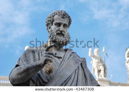 statue of St. Peter holding a key in St. Peter's Square at the Vatican - stock photo