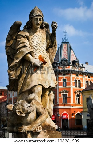 Statue of the Archangel Gabriel with historic building in the background - stock photo