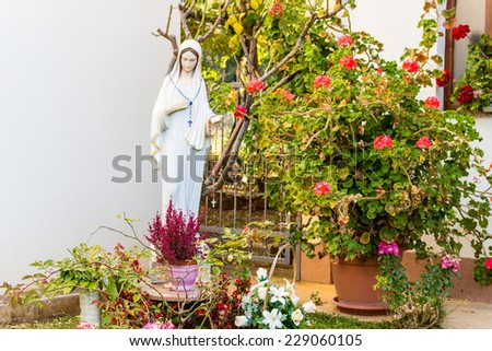 Statue of the Blessed Virgin Mary with wood prayer beads necklace in a house  garden among pots of red geraniums, roses, lilies and other plants with white wall background in  Medjugorje - stock photo