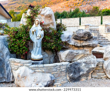 Statue of the Blessed Virgin Mary with wooden prayer beads necklace in a house rock  garden  with treesin  Medjugorje - stock photo