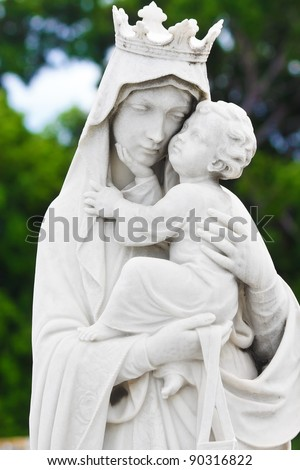 Statue of the virgin Mary carrying the baby Jesus with a diffused vegetation background - stock photo
