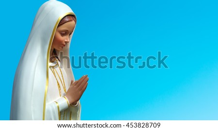 Statue of the Virgin Mary over blue sky background - stock photo