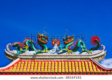 Statue of twin dragons on the roof of Chinese temple - stock photo