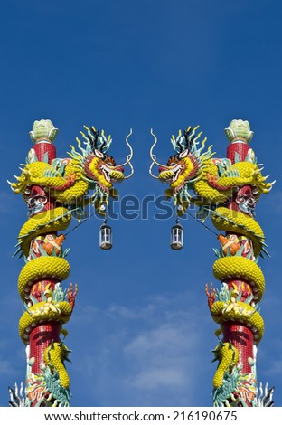 Statue of two dragons wrapped around a pole with blue sky background. - stock photo