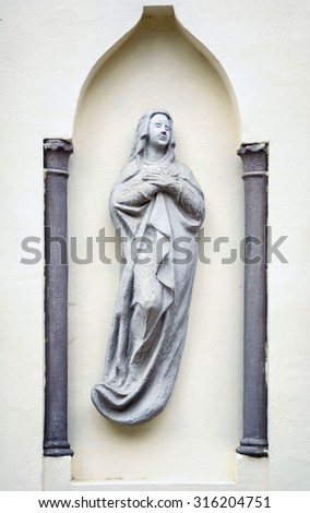 Statue of Virgin Mary in a Niche of the Wall - stock photo