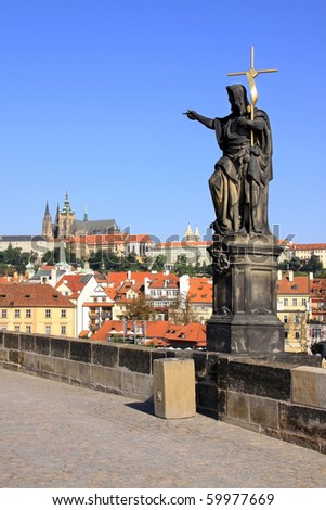 Statue on the Charles Bridge with Prague Castle - stock photo