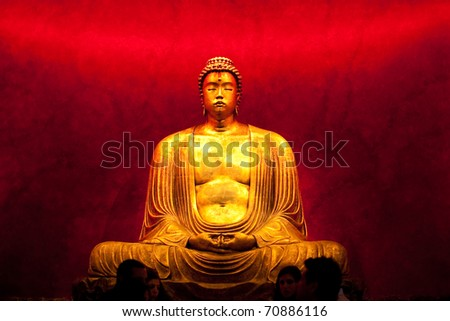 Statue representing Buddha in meditation on black background. Mass-produced plaster replica.
