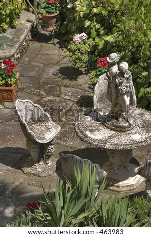 statues in a back garden with a table - stock photo