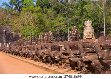 Statues of ancient khmer warrior heads carry giant snake decorating bridge to Bayon at Angkor Wat complex, Siem Reap, Cambodia.  - stock photo
