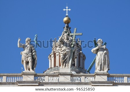 Statues of Christ, John the Baptist, and an apostle on the top of Saint Peter Basilica facade. Rome, Italy - stock photo