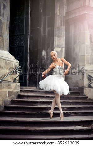 Statuesque ballerina. Young ballerina wearing all white practicing in an old castle  - stock photo