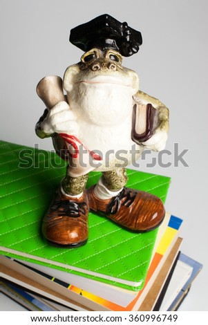 Statuette of a frog wearing a hat of the bachelor with a scroll in his hand, standing on a stack of books and notebooks